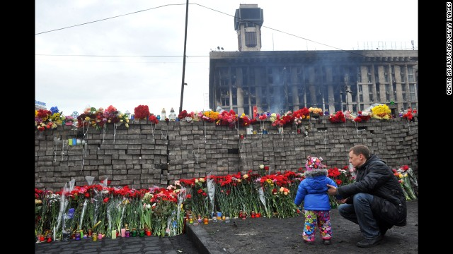 A man and the daughter lay flowers with a memorial regarding protesters killed throughout Independence Square.