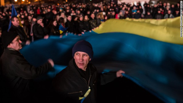 People wave a sizable Ukrainian flag within Independence Square upon Sunday, February 23.