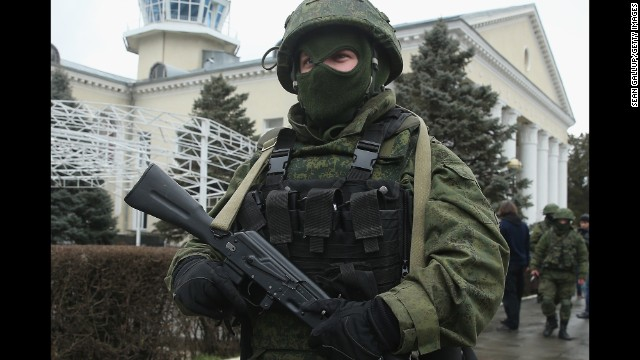 An armed man wearing absolutely no identifying military insignia patrols outside Simferopol international Airport in February 28.