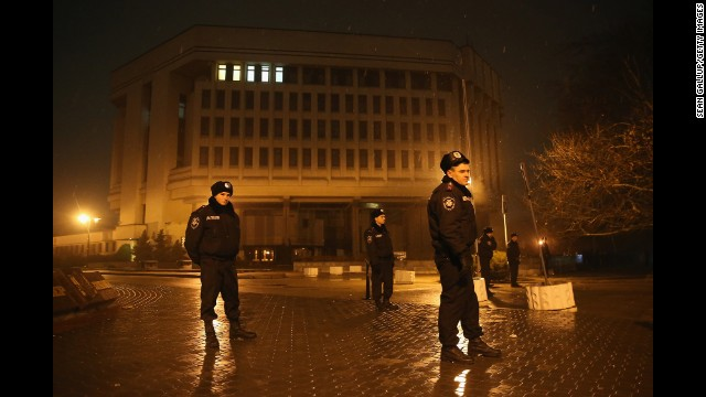 Police stand guard away from Crimea regional parliament building inside Simferopol upon Thursday, February 27.